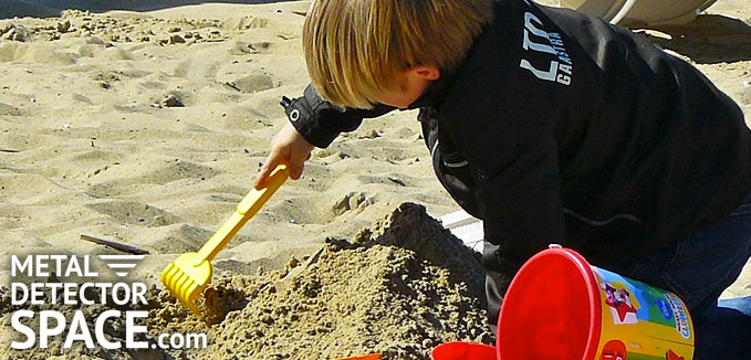 Boy at beach digging sand